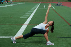 Woman Stretching on Field Royalty Free Stock Image