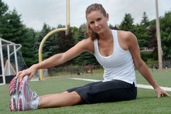 Woman Stretching on Field Royalty Free Stock Photography