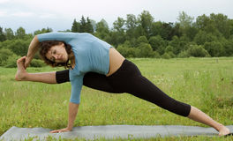 Woman stretching in field Stock Photography