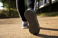 Woman stretching foot and leg. Closeup running footwear shoes. Woman stretching foot and leg after jogging in park with sunset light stock images