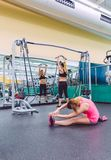 Woman stretching and friend doing dumbbell Royalty Free Stock Image