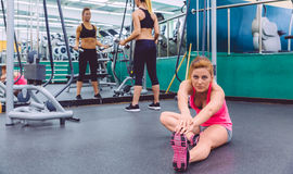 Woman stretching and friend doing dumbbell Stock Photography
