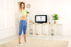 Woman Stretching In Front Of TV Stock Photography
