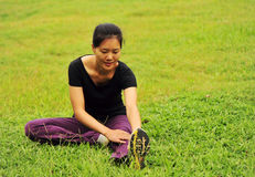 Woman stretching on grass Stock Image