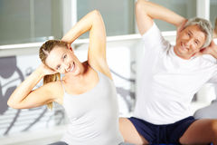 Woman stretching in group in gym Stock Photo
