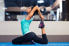 Woman stretching in gym Royalty Free Stock Photos