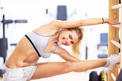 Woman stretching in gym Stock Photography