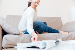 Woman stretching hand to take magazine at home Royalty Free Stock Image