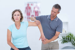Woman stretching her arm with her doctor Stock Image