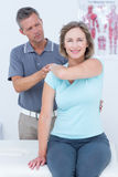 Woman stretching her arm with her doctor Stock Photos