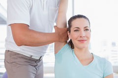 Woman stretching her arm with trainer Stock Photography