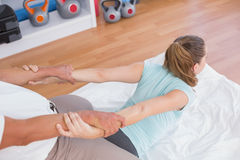 Woman stretching her arm with trainer Stock Photos