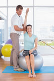 Woman stretching her arm with trainer Stock Photo