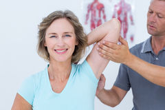 Woman stretching her arms with her doctor Stock Photography