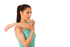 Woman stretching her arms after workout in fitness gym isolated Royalty Free Stock Images