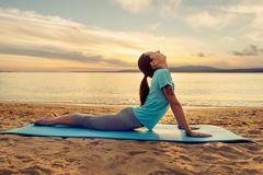 Woman stretching her back on yoga mat on beach. Sporty young woman stretching her back on yoga mat on sand beach near the sea in summer outdoor stock photography