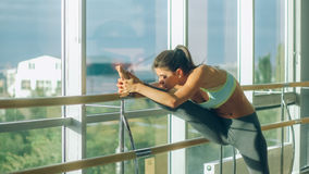 Woman stretching her leg at the barre royalty free stock images
