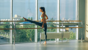 Woman stretching her leg at the barre Royalty Free Stock Image