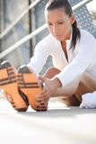 Woman stretching her leg muscles. Attractive woman sitting down stretching her legs outside Royalty Free Stock Photos