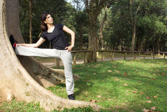 Woman Stretching Her Legs Against Tree-Horizontal. An attractive, young woman is standing in a park.  She is stretching her leg against a tree.  Horizontally Stock Photo