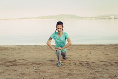 Woman stretching her legs before running on beach Stock Photos