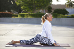 Woman stretching her legs on a yoga mat Stock Photo