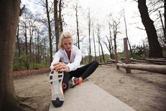 Woman stretching her muscles before a run. Fit woman stretching her legs before a run. Caucasian female model exercising in park royalty free stock photo