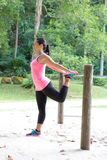 Woman stretching her thigh on a bar, exercising in the park Royalty Free Stock Image