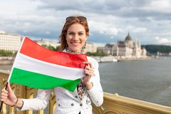 Woman stretching Hungarian flag outdoor at Budapest. Happy young woman with toothy smile stretching Hungarian flag on Margaret bridge, near to Parliament stock photography
