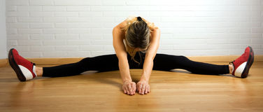 Woman Stretching Inner Thighs. Middle aged woman in white tanktop and black leggings doing exercise Stock Photo
