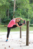 Woman stretching inside of thigh on a bar, exercising in the park Stock Photo