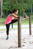Woman stretching inside of thigh on a bar, exercising in the park Royalty Free Stock Photo