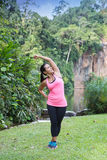 Woman stretching left side of body after exercising in outdoor park Royalty Free Stock Image