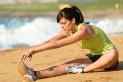 Woman stretching leg on beach Royalty Free Stock Images