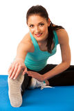 Woman stretching legs on blue mat, isolated over white backgroun Stock Image