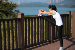 Woman stretching legs in city park Stock Photos