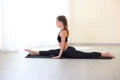 Woman Stretching Legs in Splits Position in bright room. Profile happy young woman doing splitting legs apart twin in bright gym. Working on Flexbility and stock images