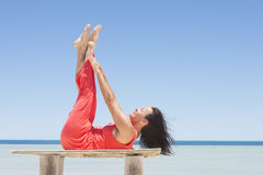 Woman stretching legs tropical beach. Portrait attractive mature woman in red summer dress stretching legs up on table at beach, enjoying tropical holiday Stock Image