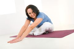 Woman stretching on mat Royalty Free Stock Images