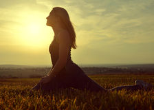 Woman stretching on a meadow at sunset Stock Photo