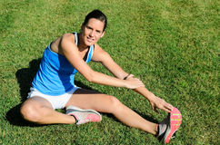 Woman Stretching Muscles. Young and beautiful female athlete stretching the hamstring muscles, smiling and looking at camera. She graps the foot to do the Stock Images