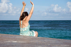 Woman stretching by the ocean Royalty Free Stock Image