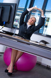 Woman stretching in office Stock Images