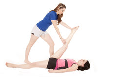 Woman stretching others leg Royalty Free Stock Images