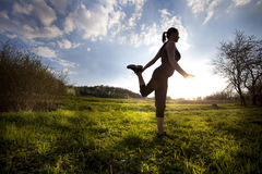 Woman stretching out on the field Royalty Free Stock Images