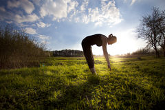 Woman stretching out on the field Stock Photo