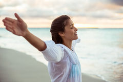 Woman stretching out her arms. On the beach Stock Image