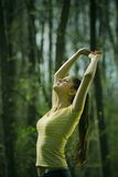 Woman stretching outdoors. Casually dressed young woman stretching her hands above her head in a natural outdoor setting Stock Photography