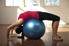Woman stretching over a fitness ball Royalty Free Stock Photo