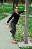 Woman stretching at the park. Young woman happily stretching at the park Royalty Free Stock Image